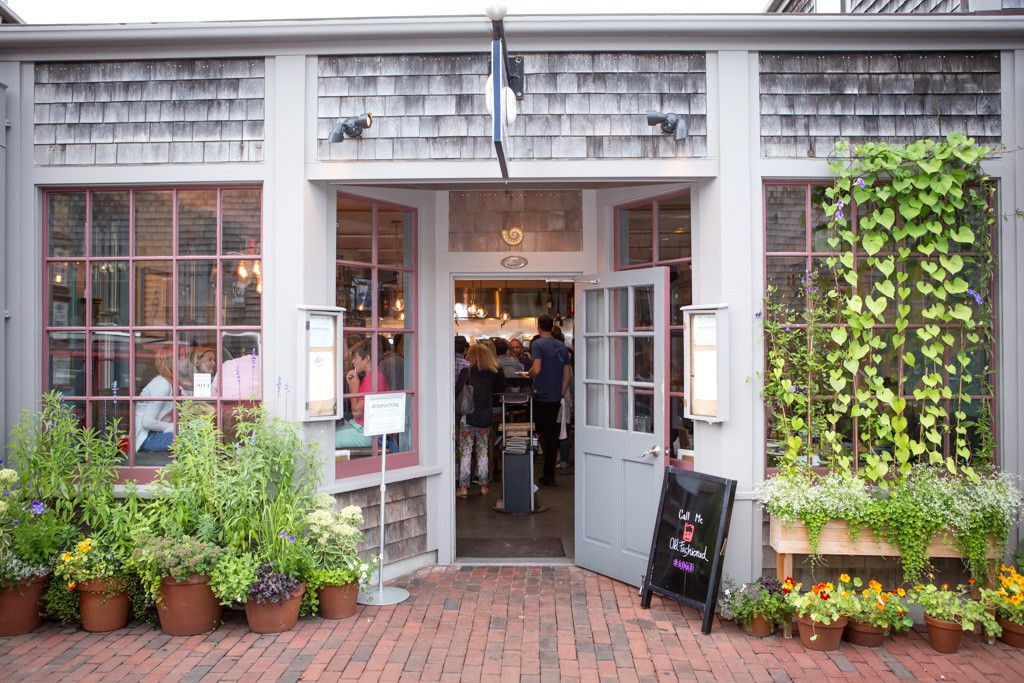 An exterior view of the Nautilus, featuring worn gray shingles, vines and other greenery, and an open door, offering a glimpse of the crowded restaurant within