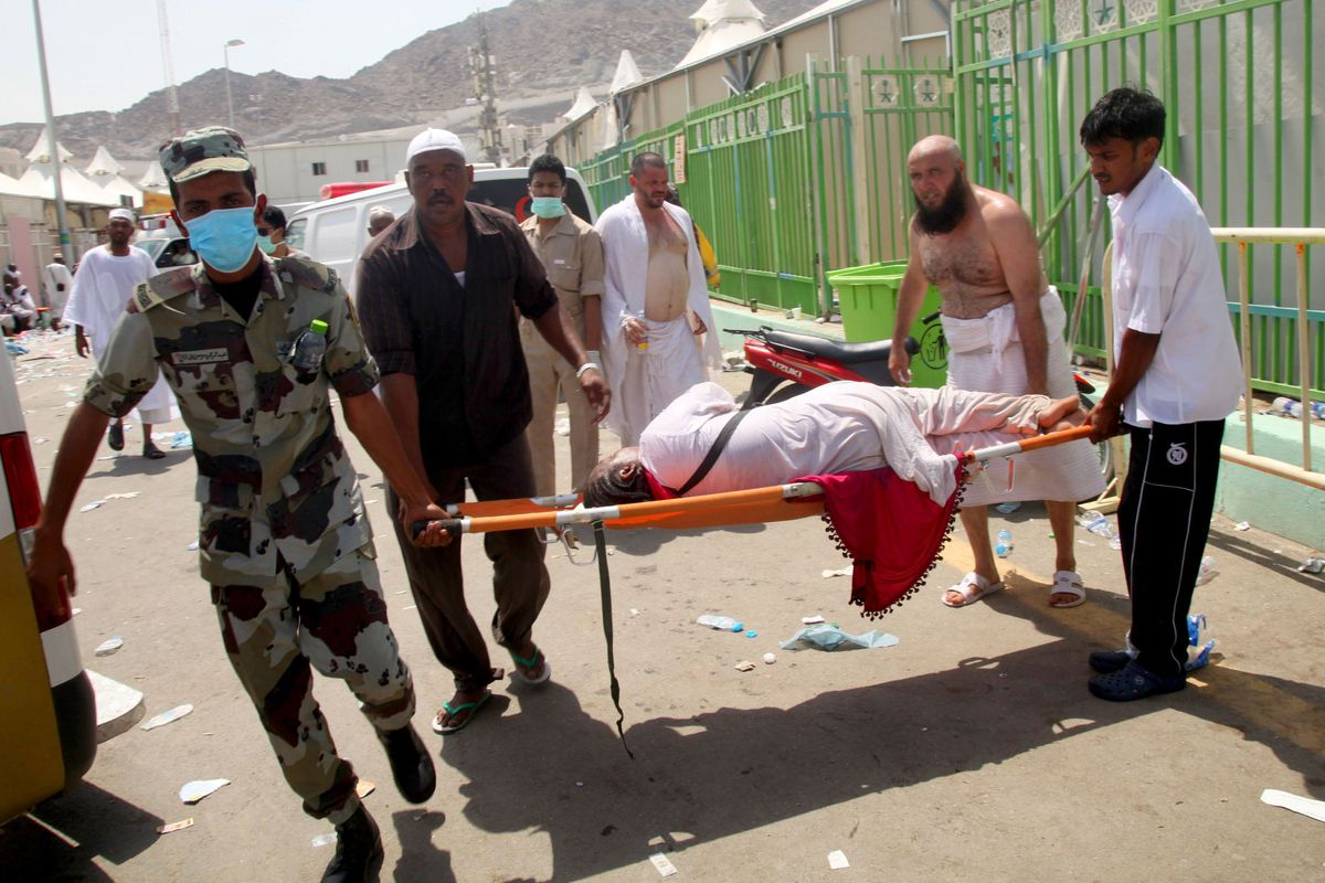 Hajj pilgrims and emergency personnel carry a woman injured during the Mina stampede.