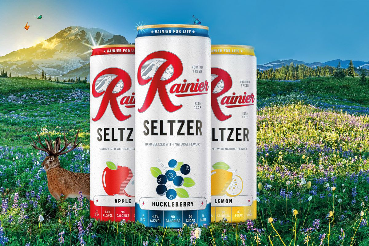 A photo composite showing three cans of Rainier Seltzer in the foreground (huckleberry up front, apple to the left, and lemon to the right), against a photo illustration of a field in front of Mount Rainier, where a rabbit is hanging out