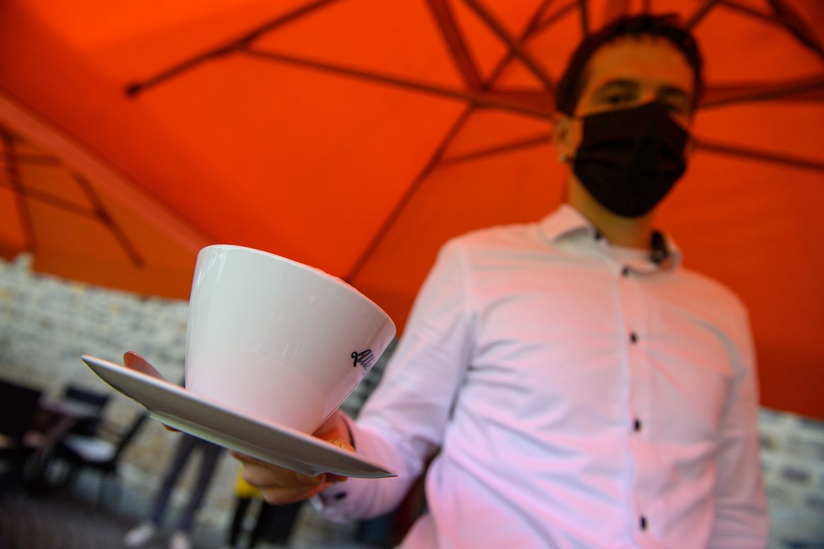 A masked server delivers a cup of coffee