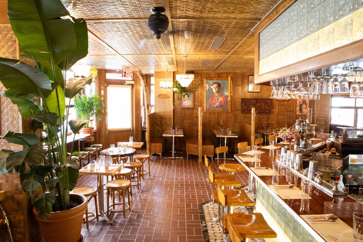 The interior of a restaurant with light brown wood, several tables and chairs, a bar counter, and paintings in the distance