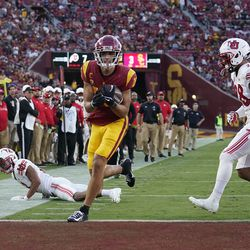 Southern California wide receiver Drake London, center, scores past Utah safety Brandon McKinney, right, during the first half of an NCAA college football game Saturday, Oct. 9, 2021, in Los Angeles.
