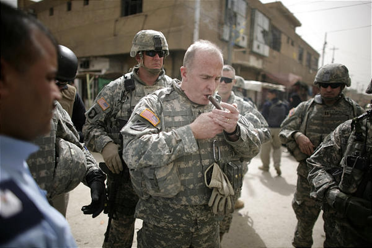 Maj. Gen. Rick Lynch, center, commander of the U.S. 3rd Infantry Division, lights a cigar in March 2008 at the market in Iskandariyah, 30 miles south of Baghdad, Iraq.