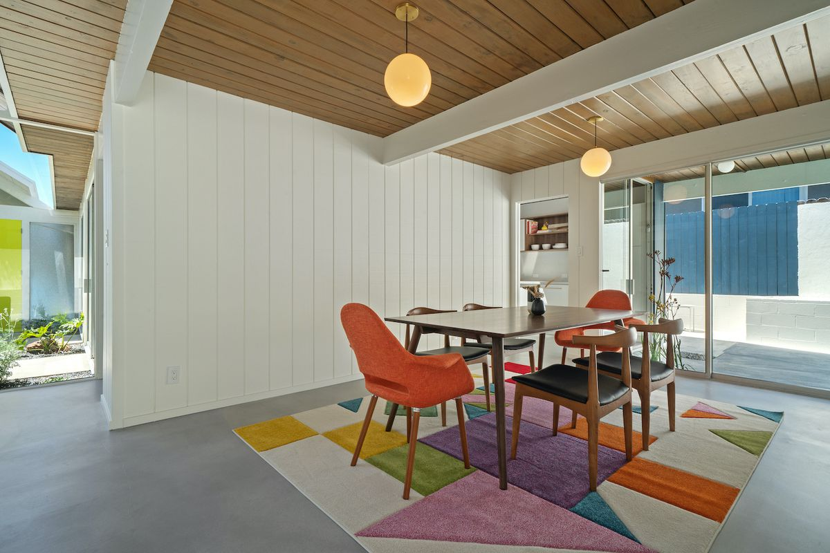 An open and airy dining area with midcentury dining table and dining chairs. Two glove light fixtures hang from the beamed ceiling.
