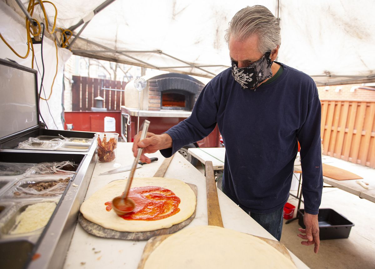 A man in a fabric face mask ladles sauce onto pizza dough.