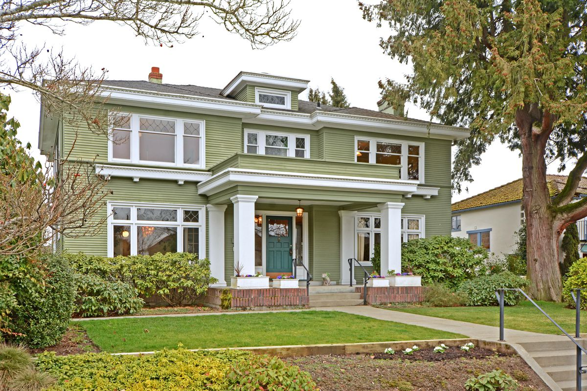 An imposing, green, two-story house with a large front portico