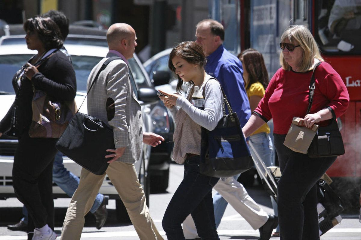 In this photo taken Wednesday, June, 29, 2010, a woman text messages while walking across the street in San Francisco.