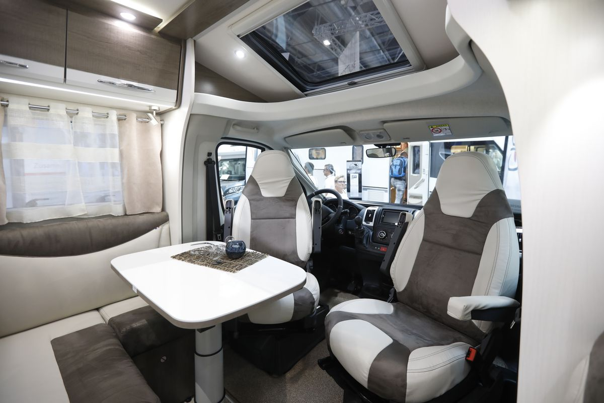 The front area of the motorhome has two swivel front cab chairs turned to face a rear table and dinette area.