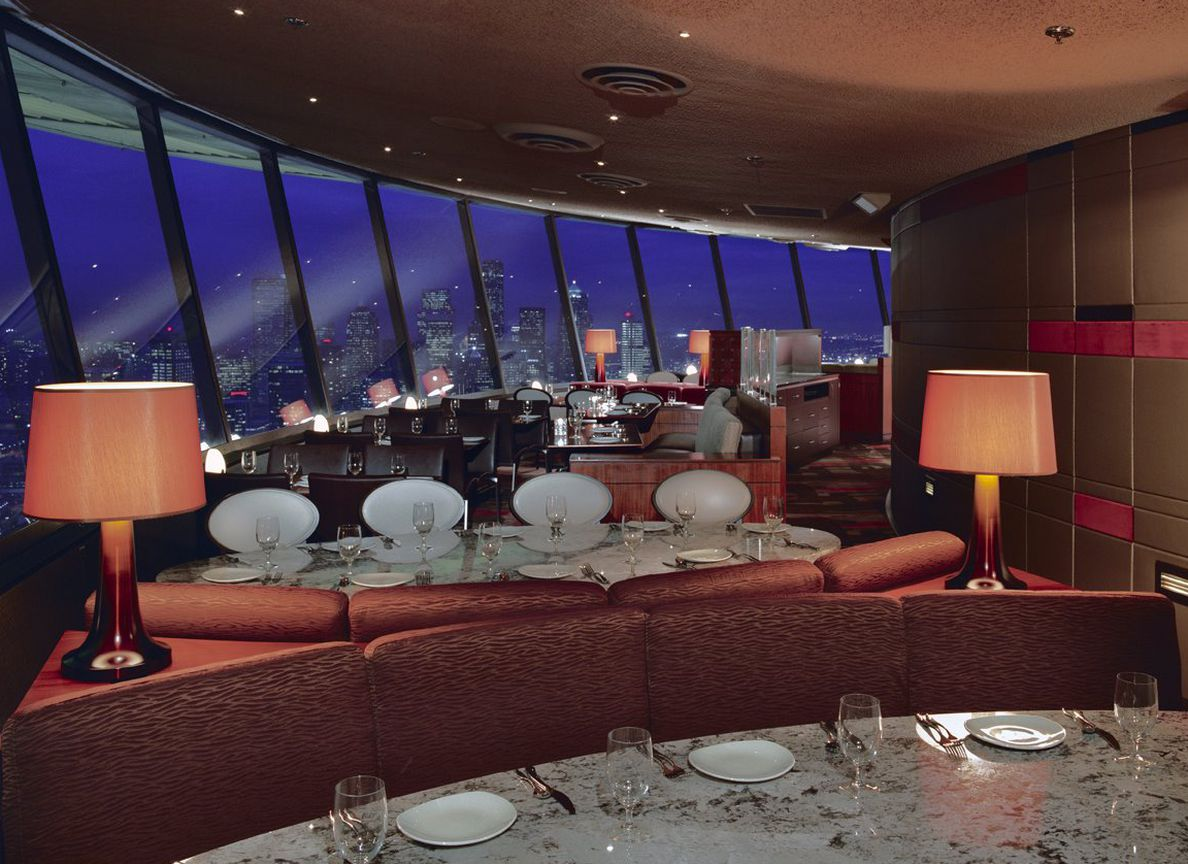 A view of the low-lit dining room in the currently-closed SkyCity Restaurant, featuring nighttime views of the city and banquettes.