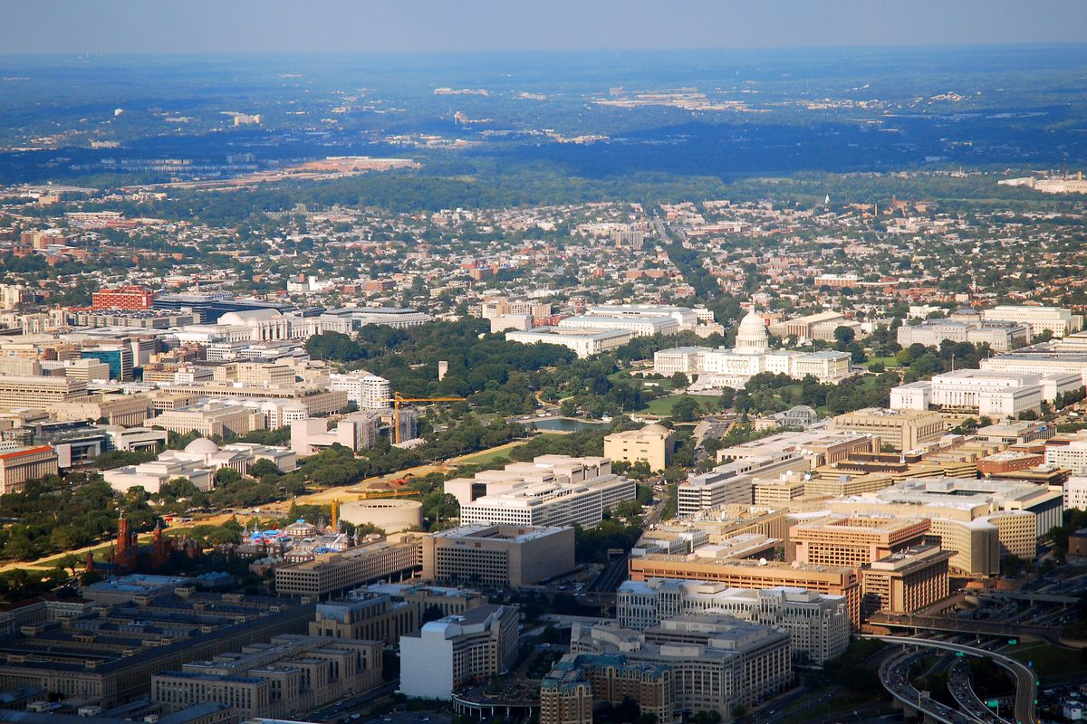 An aerial view of D.C. and its regional surroundings, showing the National Mall, the U.S. Capitol, downtown, and farther out.