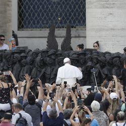 """Pope Francis unveils the sculpture on the theme of refugees and migration, """"Angels Unawares."""" by Canadian sculptor Timothy P. Schmalz, on the occasion of the Migrant and Refugee World Day, in St. Peter's Square, at the Vatican, Sunday, Sept. 29, 2019."""