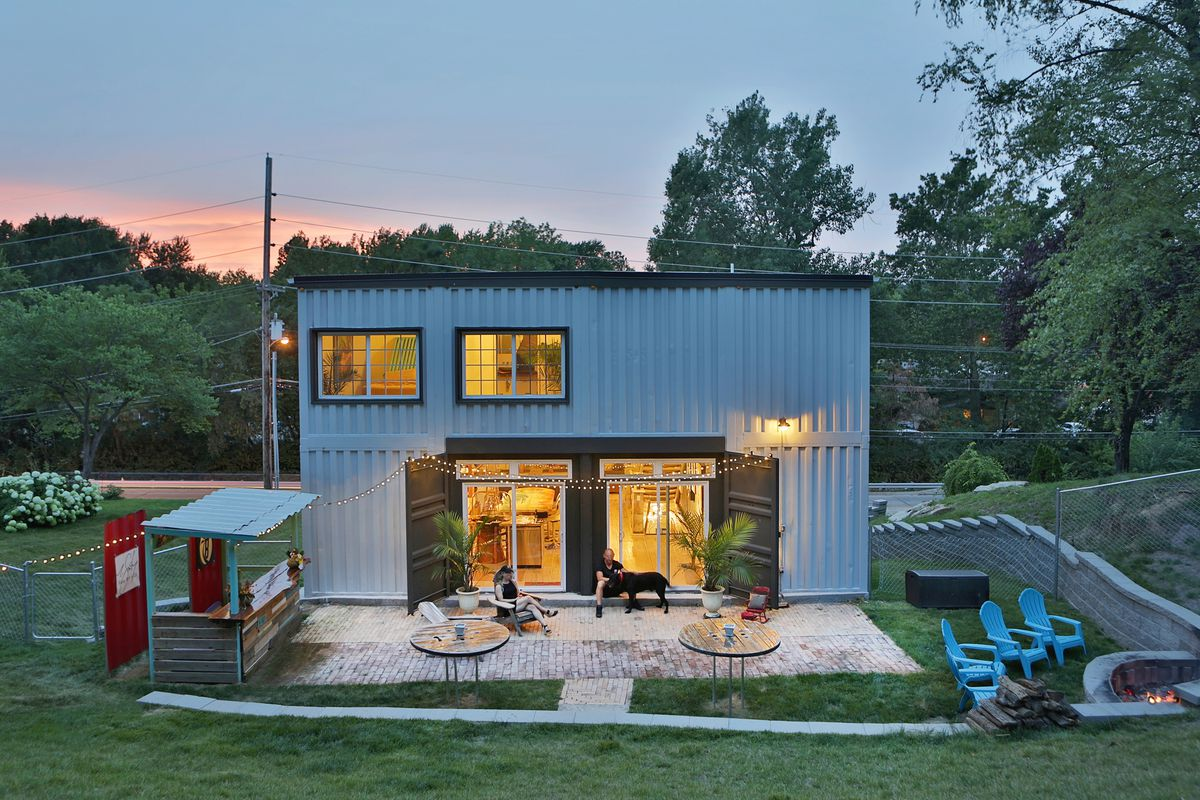 The shipping container's metal is visible on the back of the house. You can see two large sliding doors the Smithey's installed, opening the lower level to the patio.