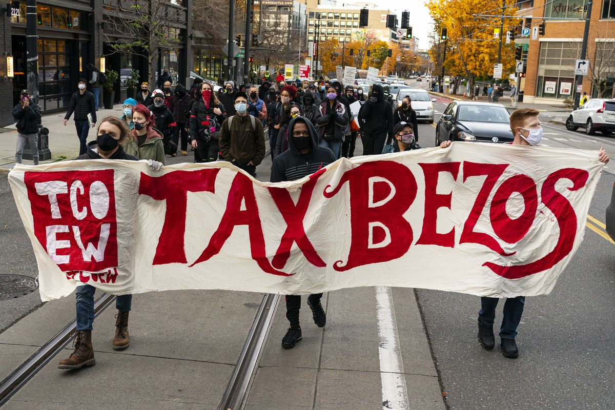 """Demonstrators protest outside Amazon headquarters, holding a sign reading """"Tax Bezos""""."""