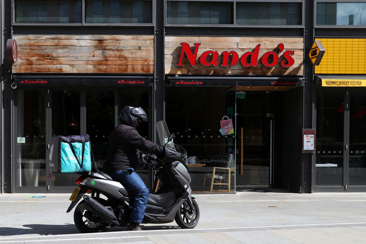 A Nandos restaurant in England with a delivery rider outside