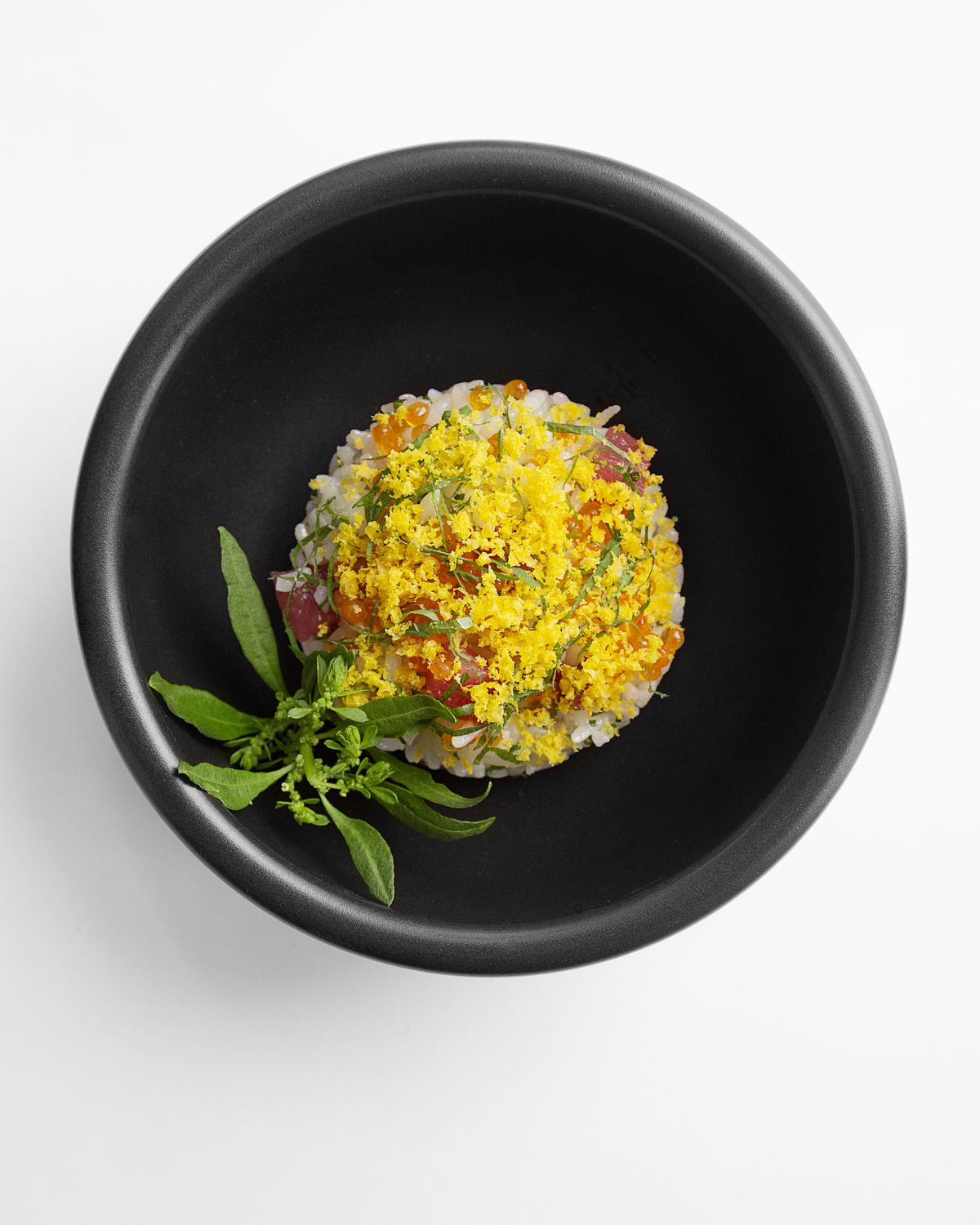 A black bowl with some yellow powder, small orange balls, and a green leaves
