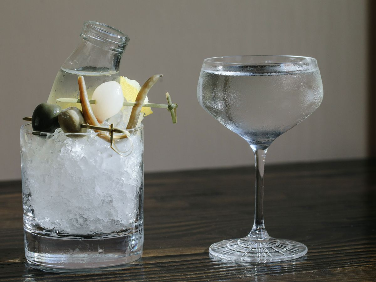 A clear martini in a glass sits next to a sidecar with various garnishes