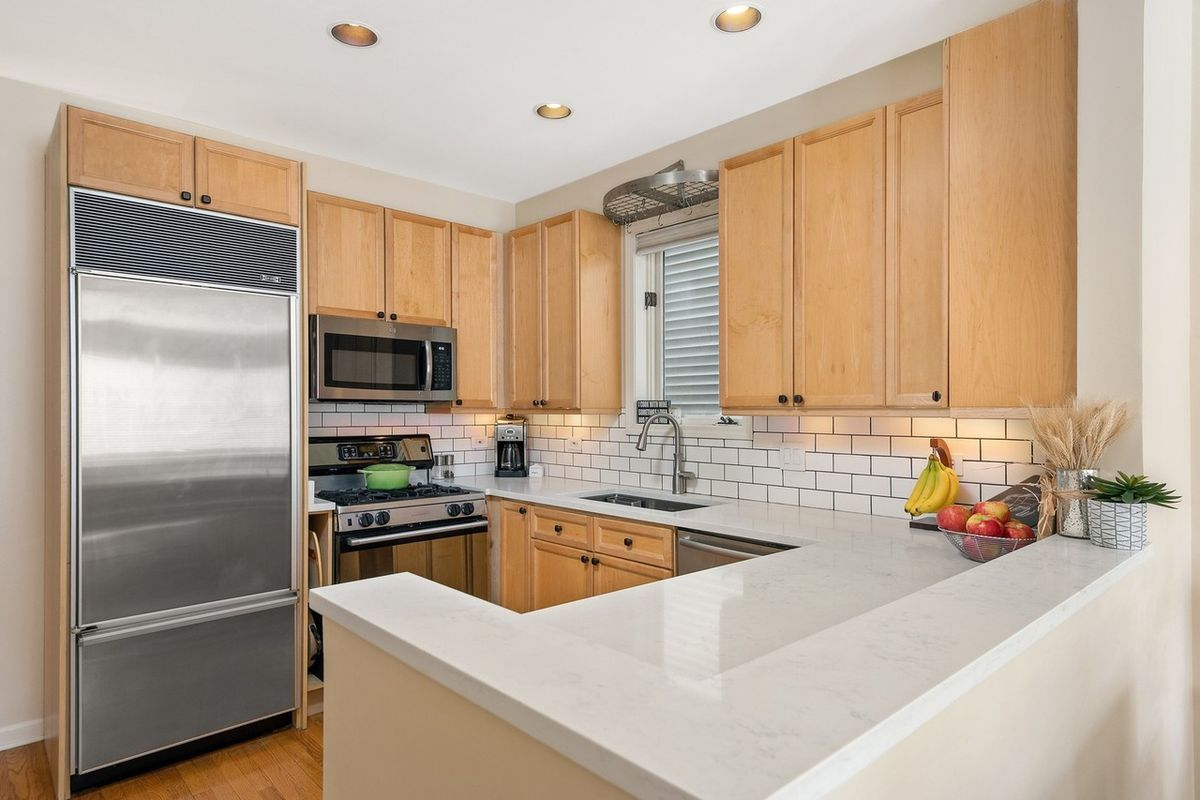 The kitchen has light colored wood cabinets, a white countertop and subway tile backspash.
