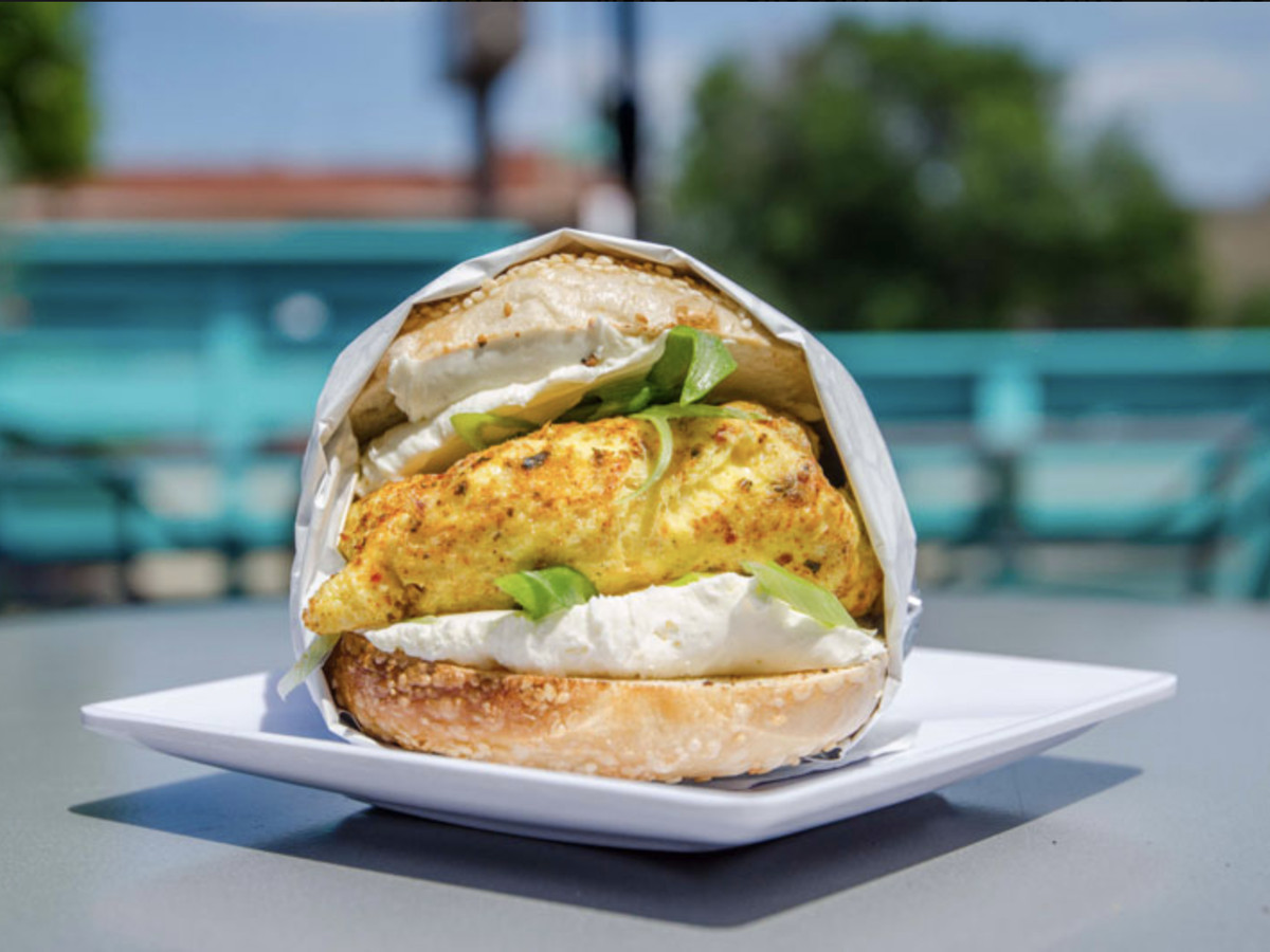 A scrambled egg sandwich with greens on a bun sits on a white plate.