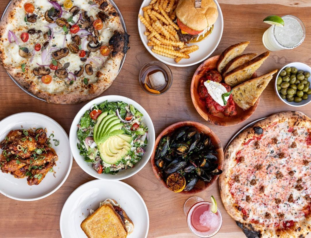 A table topped with two full pizzas, a burger, toast with dip, avocado salad, sandwich, mussels, and drinks