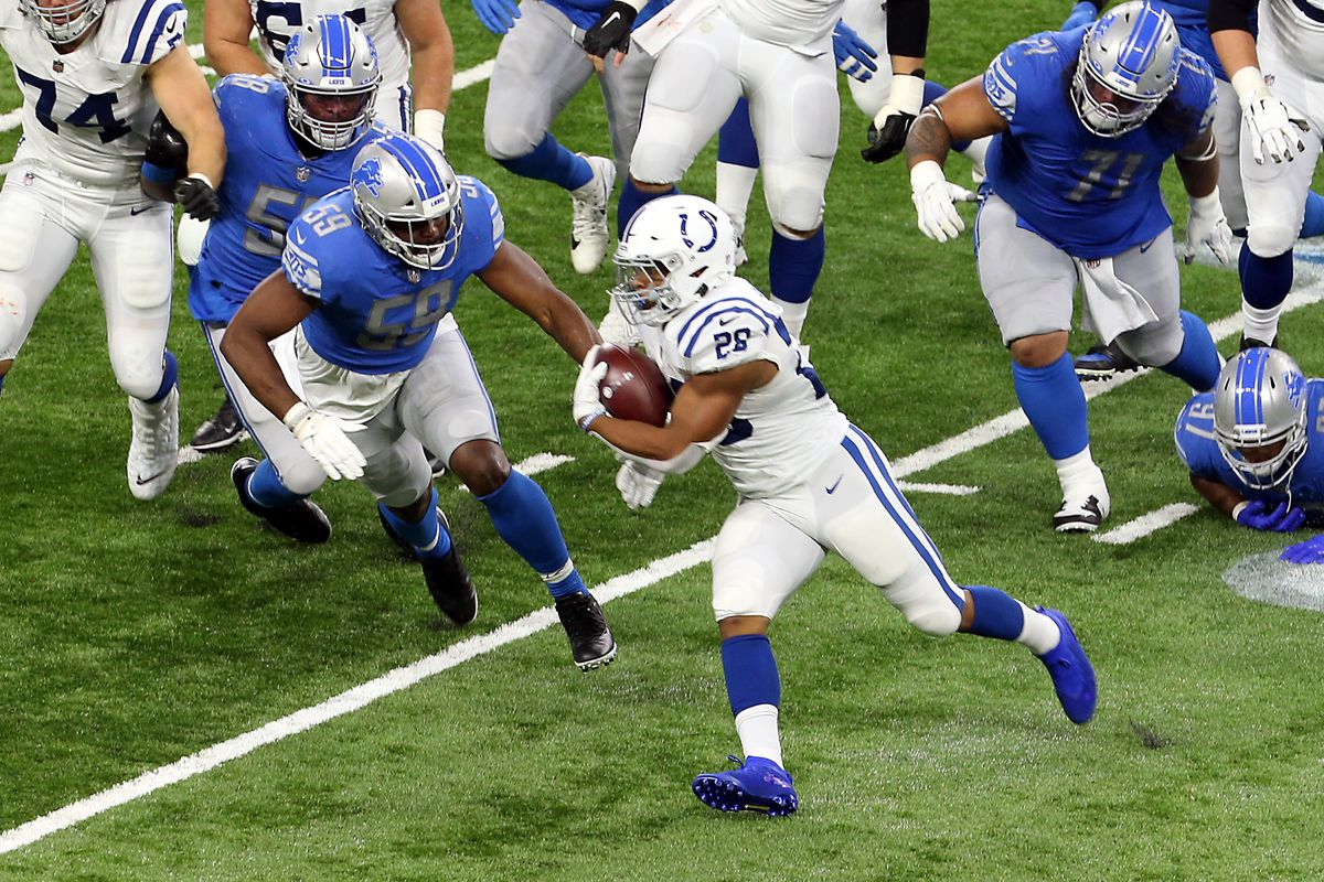 Indianapolis Colts running back Jonathan Taylor (28) carries the ball under the pressure of Detroit Lions defense during the first half of an NFL football game against the Detroit Lions in Detroit, Michigan USA, on Sunday, November 1, 2020.