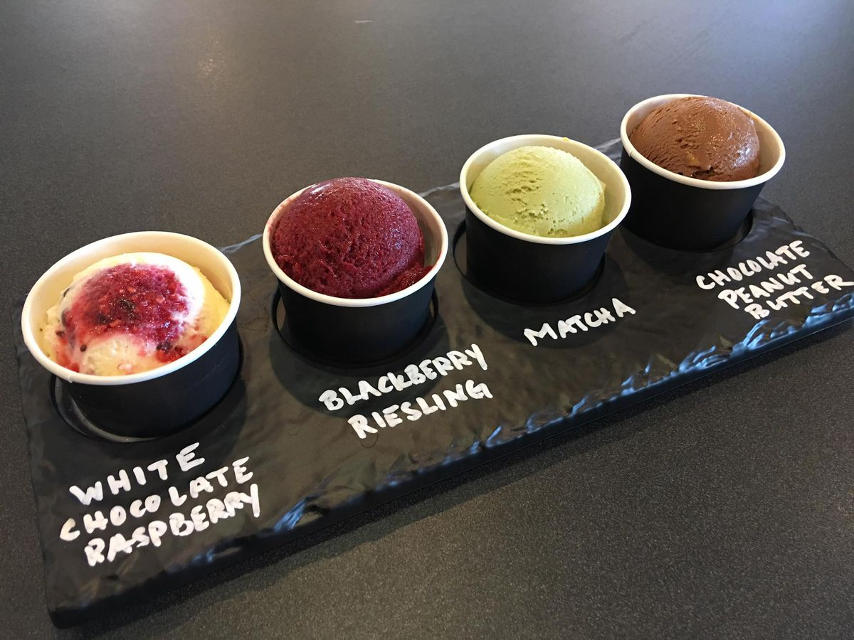 A flight (or tray) with four cups of four different ice cream flavors