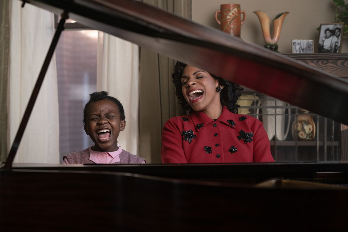 A woman and a child sing at a piano.
