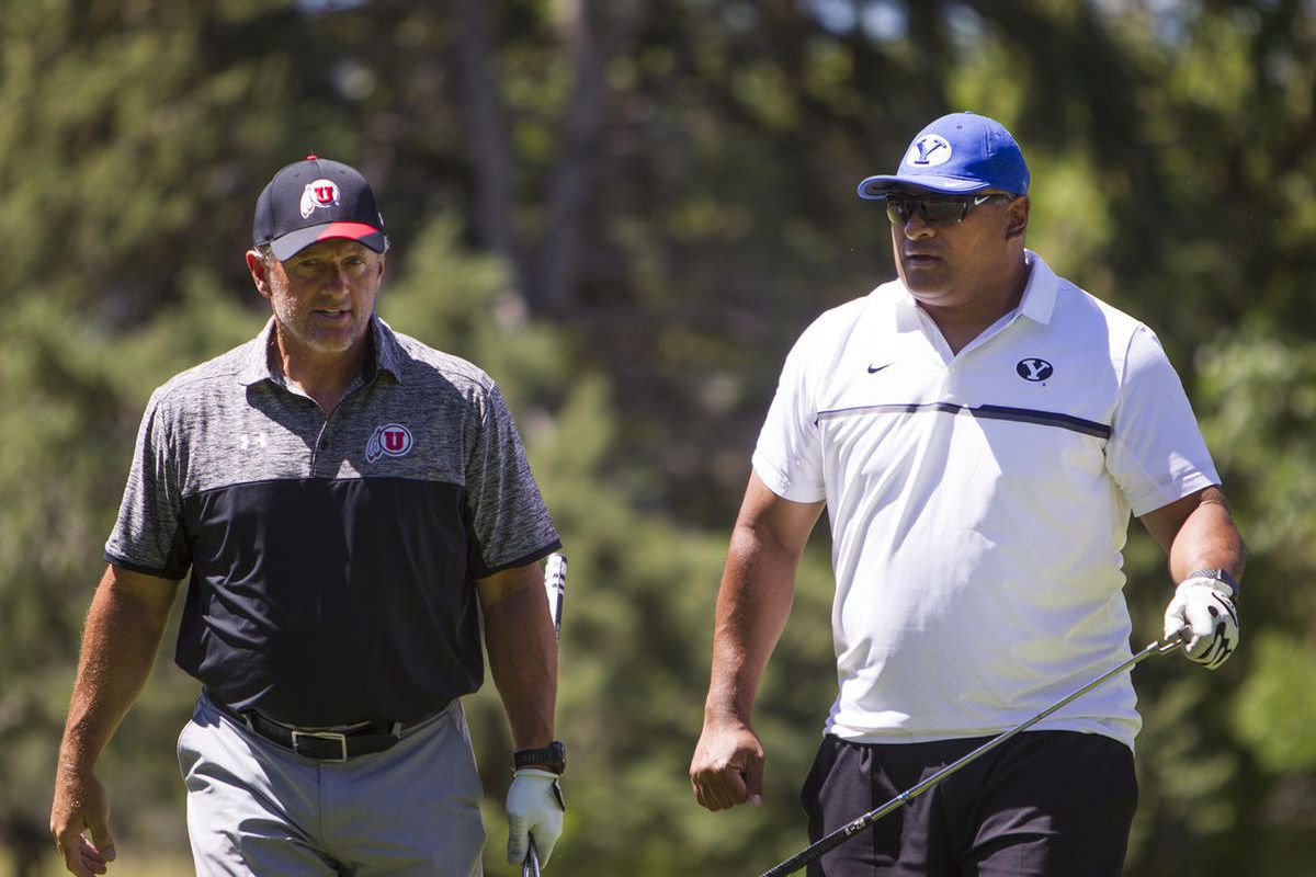 University of Utah's Head Football Coach Kyle Whittingham, left, Brigham Young University's Head Football Coach Kalani Sitake walk back to the golf cart after teeing off during the annual National Kidney Foundation fundraiser and golf invitational at Hidd