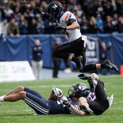 BYU defensive back Hayden Livingston receives a pass while getting tackled by Boise State cornerback Kekaula Kaniho as Alexander Teubner (34) jumps over during an NCAA college football game at LaVell Edwards Stadium in Provo on Saturday, Oct. 9, 2021.