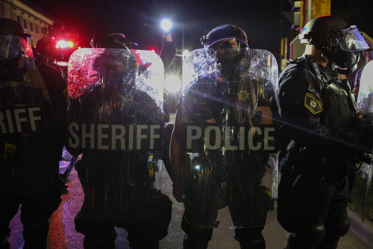 """Officers standing behind handheld shields, one that reads """"sheriff"""" and one that reads """"police."""""""