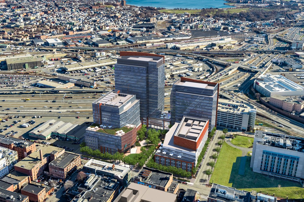 An aerial view of four new buildings amid an urban landscape that includes highways and a harbor.