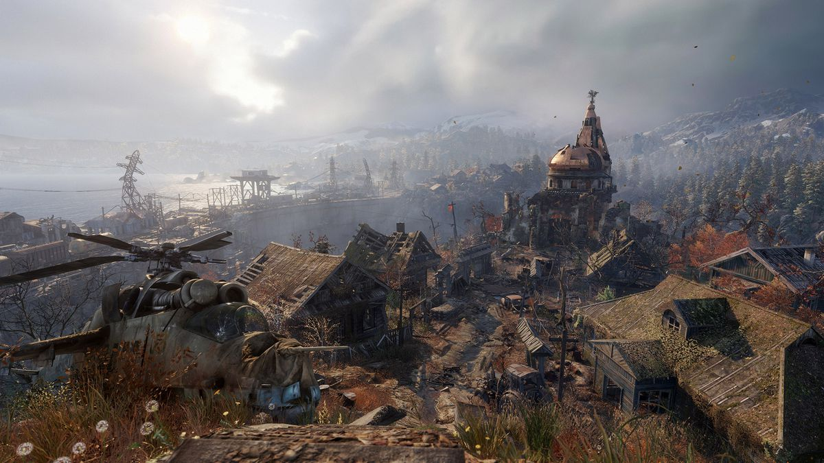 This screenshot from Metro Exodus shows off a huge vista in the game. It includes shots of a dilapidated village, a crashed helicopter and mountains and forests in the distance.