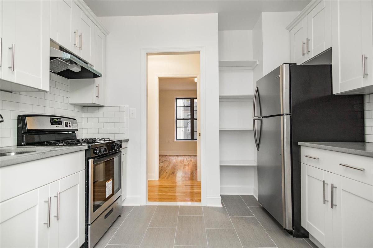 A kitchen with white cabinetry and white walls.