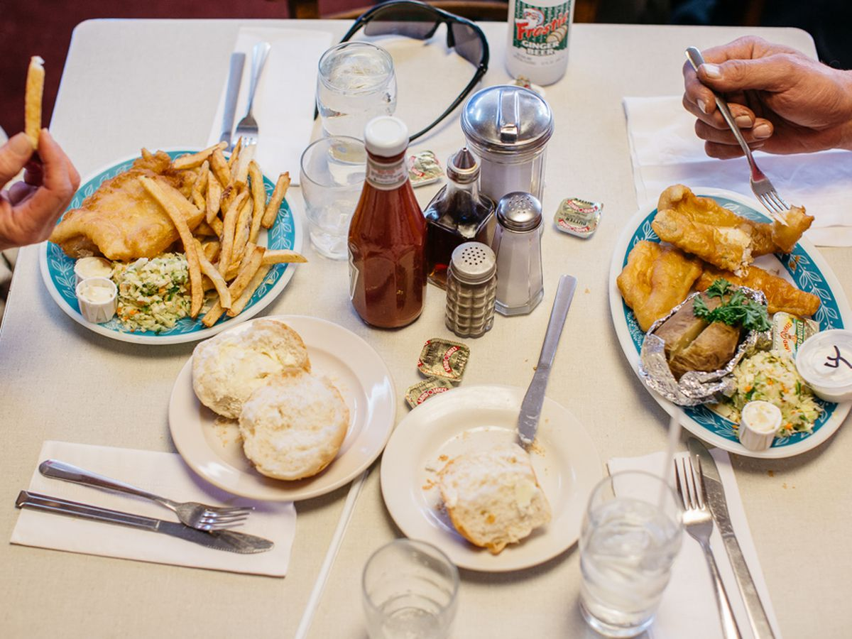 Customers eat plates of fish and chips with buttered rolls at Scotty Simpson's.