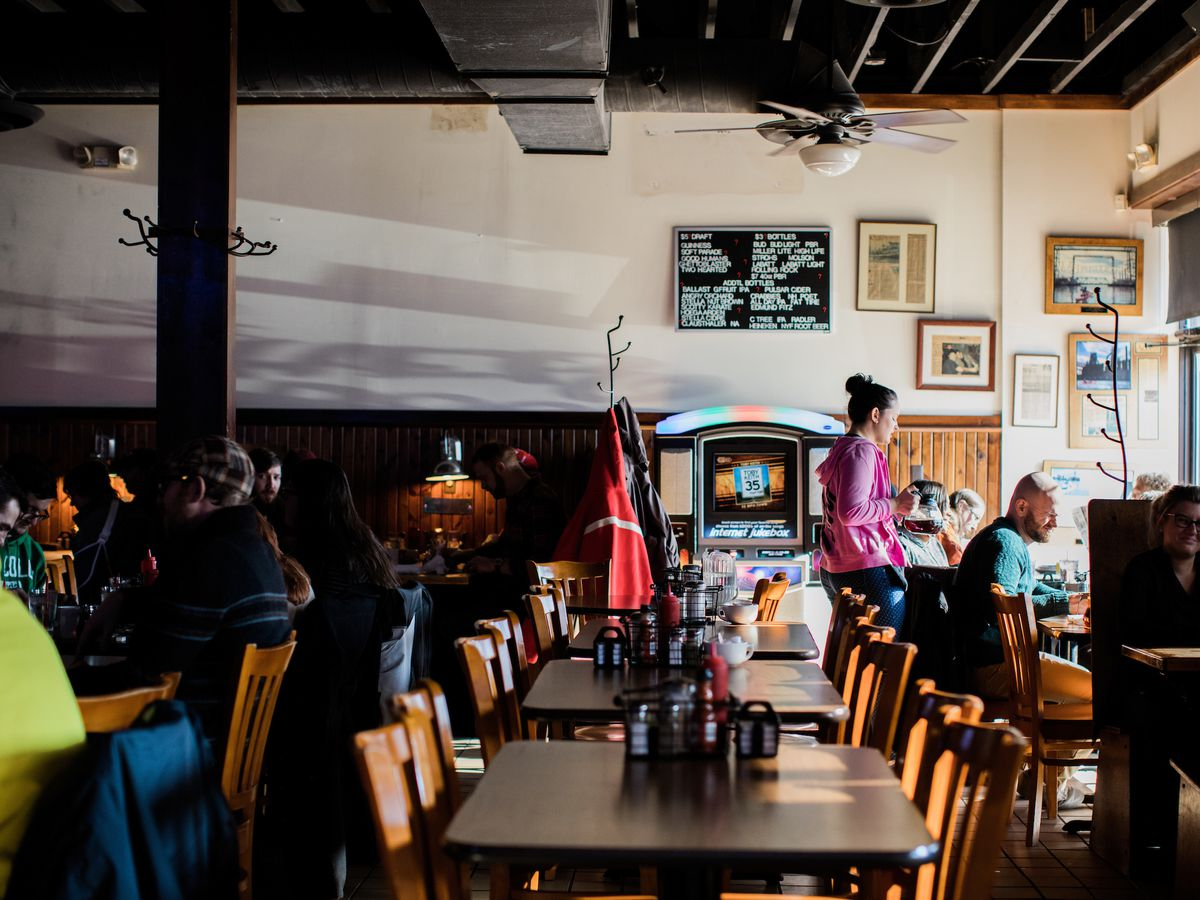 A waitress in a pink sweater delivers food to a table near windows with sun streaming into the dim bar.