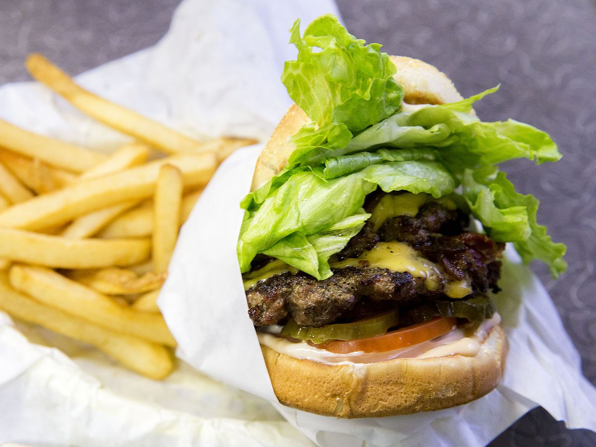 A closeup shot of a Zippy's cheeseburger with tomato, lettuce, and fries on the side.