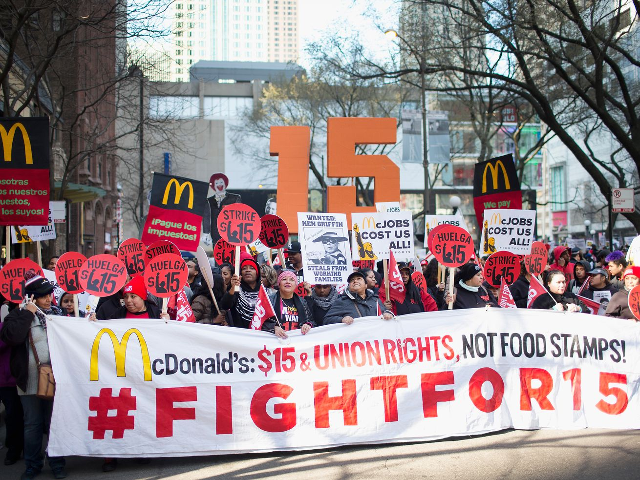 McDonald's workers hold a Fight for 15 banner.