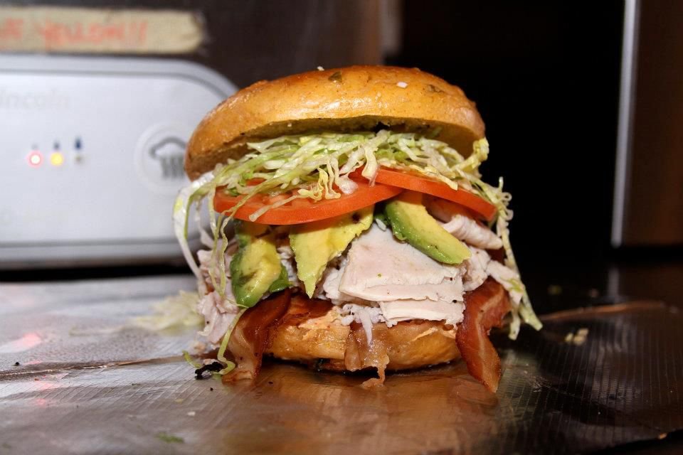 A bagel sandwich absolutely filled with turkey and other ingredients on a metal countertop