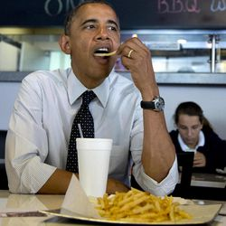 President Barack Obama pops a french fry into his mouth as he visits with students at OMG! Burgers, Thursday, Sept. 20, 2012, in Miami, Fla.