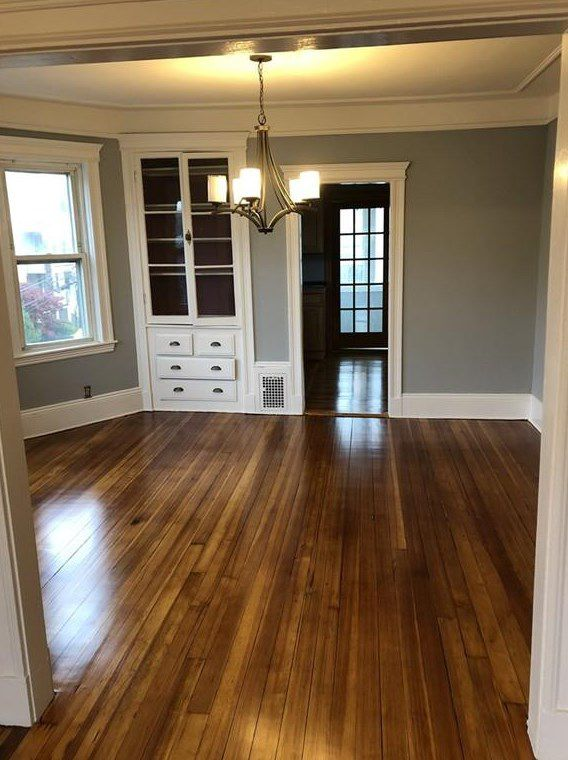 An empty living room through an entryway, and there's a hutch with drawers in the background.