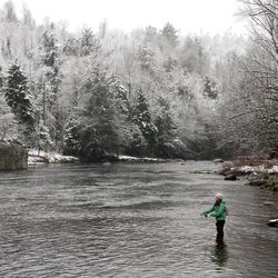 A woman fishes on the West Branch of the AuSable River in Wilmington, N.Y., after a snowfall on Sunday, April 22, 2012.