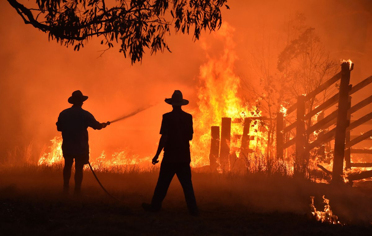 Residents defend a property from a bushfire at Hillsville near Taree, 350km north of Sydney on November 12, 2019.
