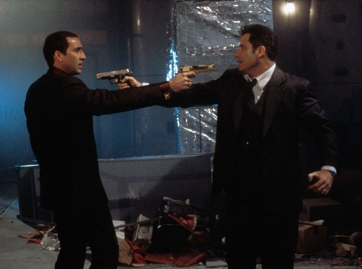 The two men point guns at each other.