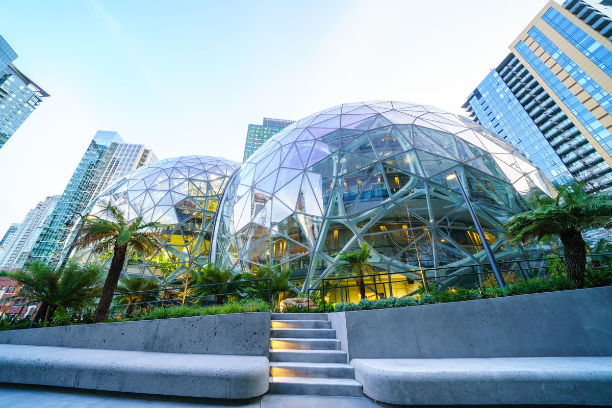 The Amazon Spheres in downtown Seattle shown from a low-angle lens on a sunny day, with foliage visible within the buildings