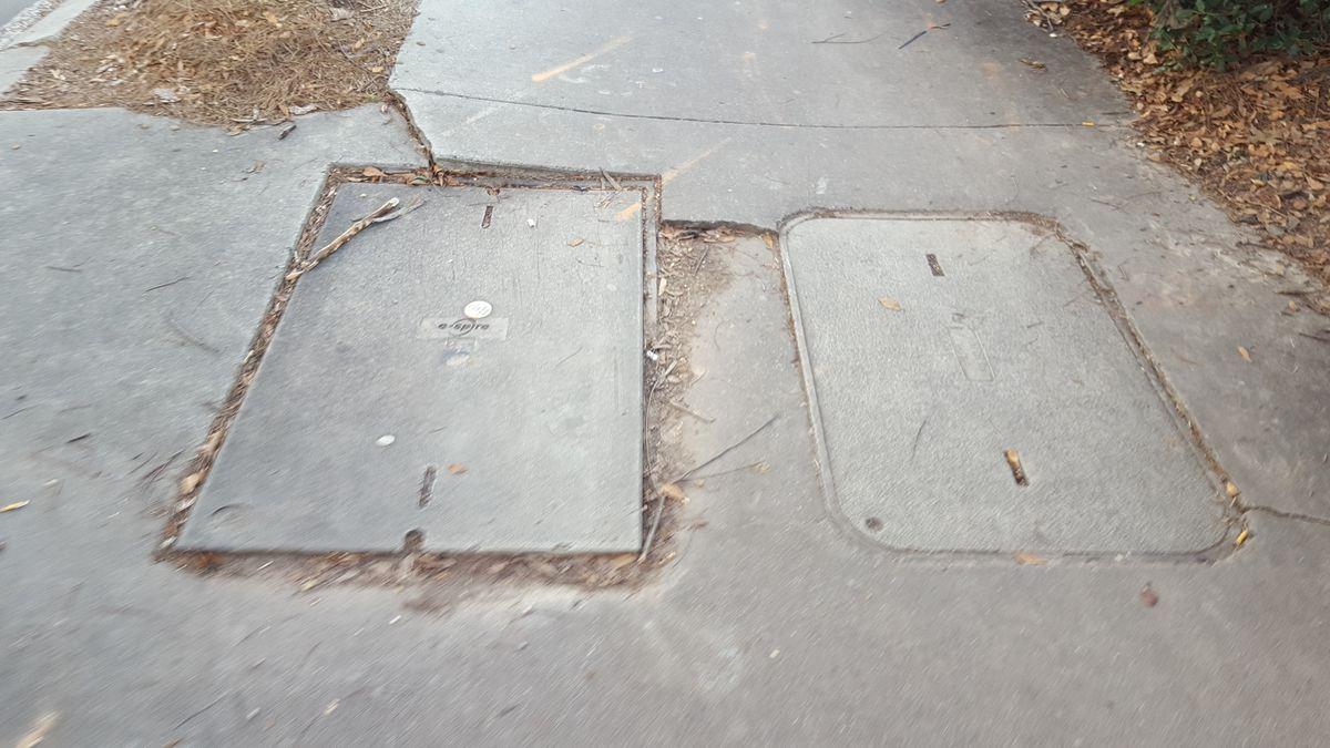 Utilities embedded in a sidewalk act as tripping hazards.