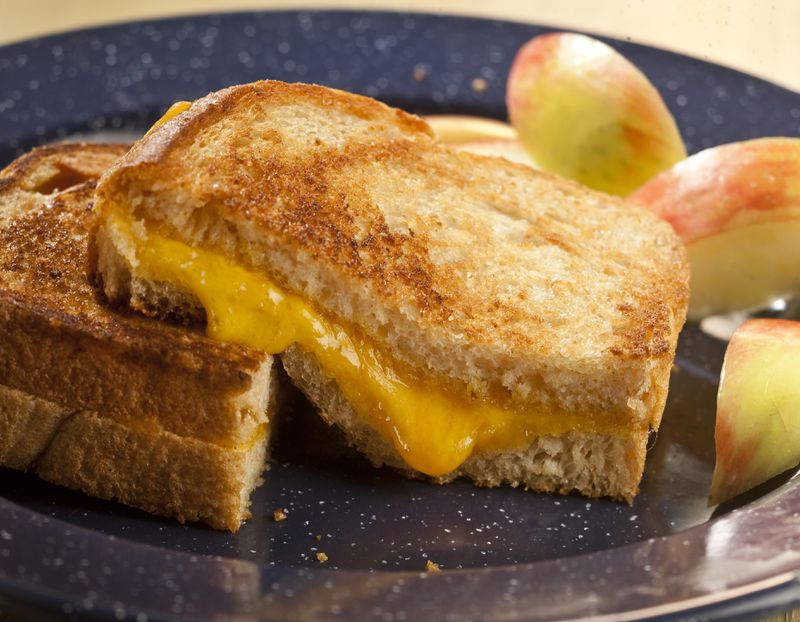 A grilled cheese sandwich with a side of apples