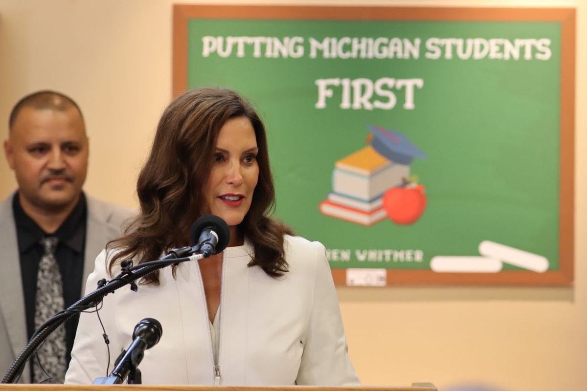 """Michigan Governor Gretchen Whitmer speaks into a microphone in front of a sign that reads, """"Putting Michigan Students First."""" There is a man in a grey suit behind her right shoulder."""