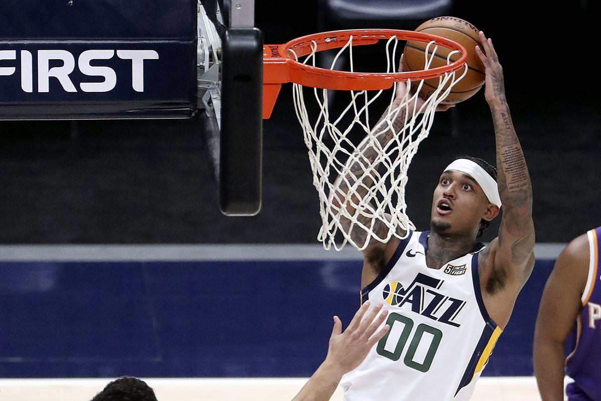 Utah Jazz guard Jordan Clarkson (00) dunks the ball as Phoenix Suns guard Devin Booker (1) and Utah Jazz center Derrick Favors (15) watch during a preseason NBA game at the Vivint Smart Home Arena in Salt Lake City on Monday, Dec. 14, 2020.