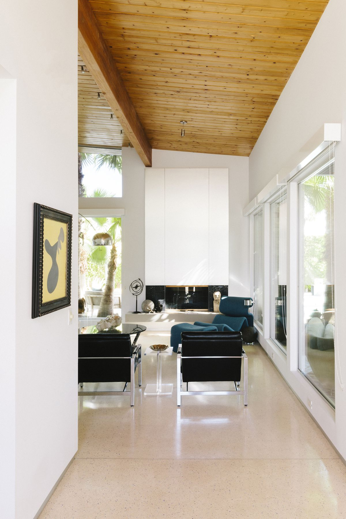 A hallway that opens up to a living area. The ceiling is wooden and the walls are painted white. The living area has a blue armchair and two black chairs. There are windows along two walls.