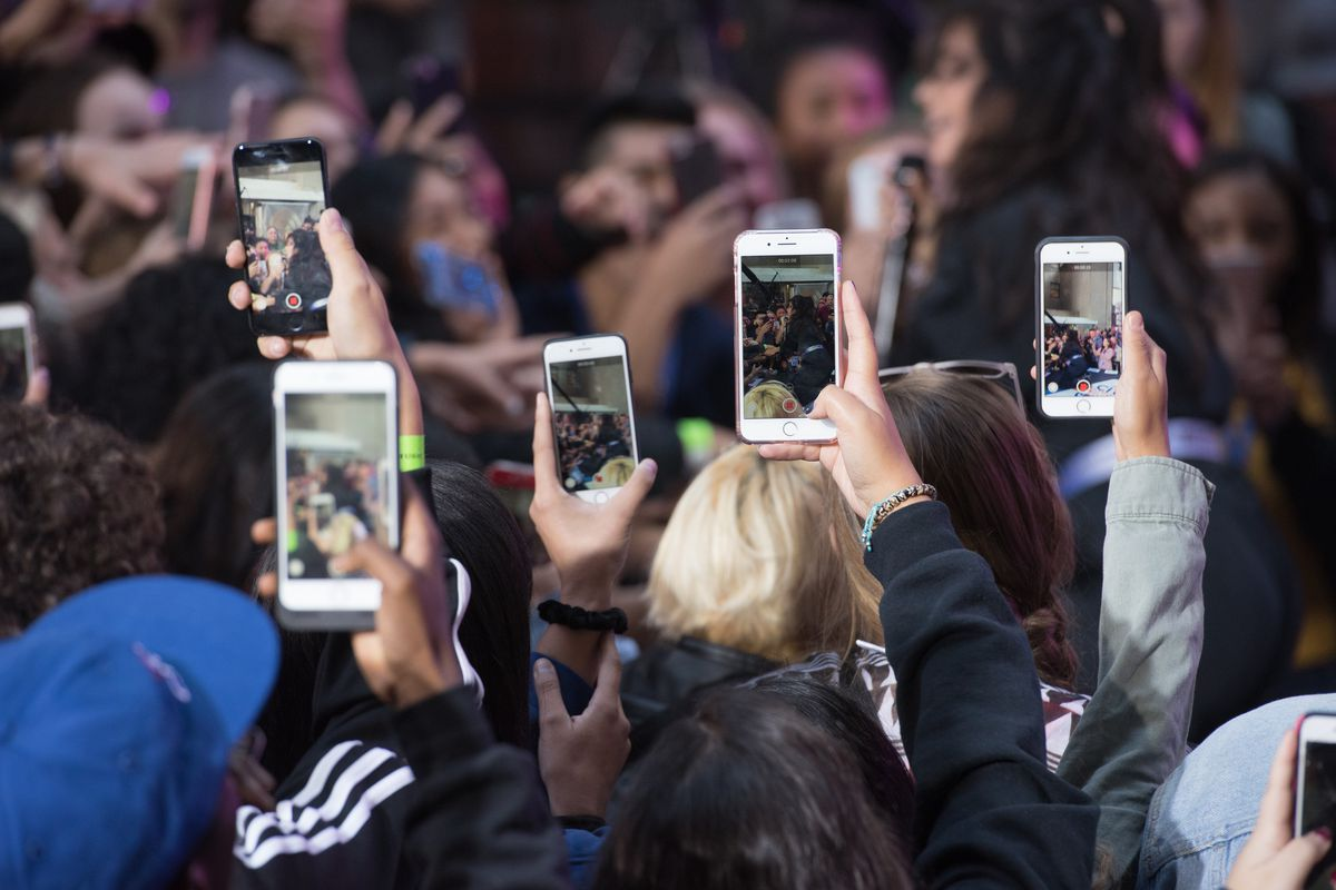 A crowd of people hold smartphones up to record video