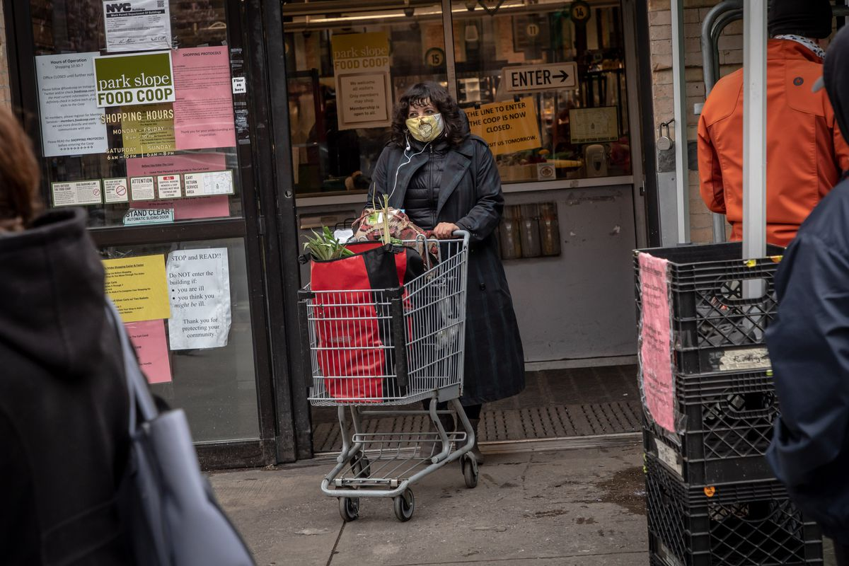 A woman wearing a masks exists the Park Slope Food Coop with a grocery cart.